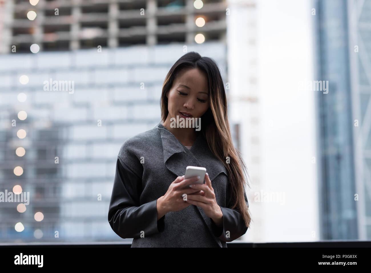 Geschäftsfrau, die mit ihrem Mobiltelefon Stockbild