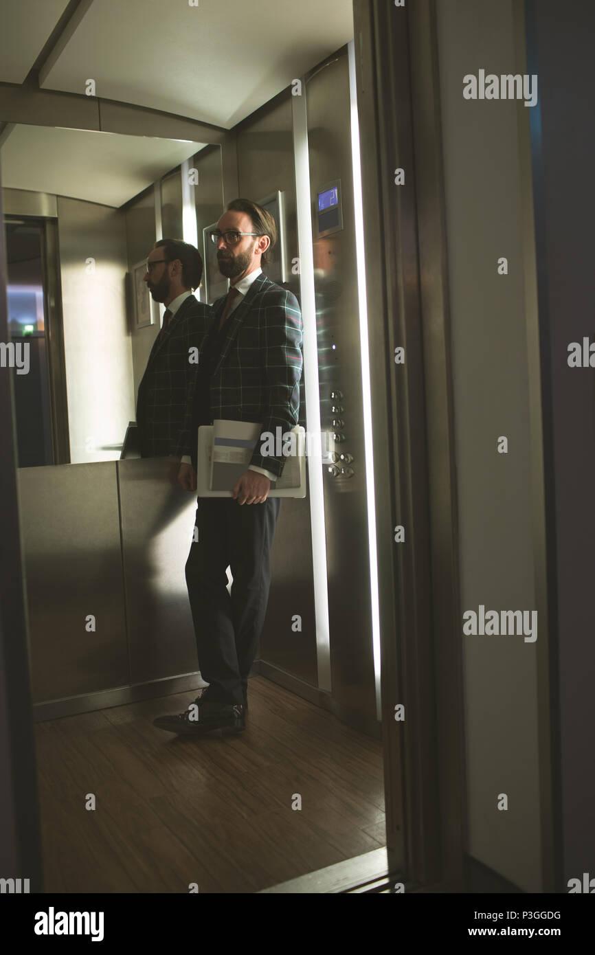 Unternehmer stehen im Aufzug Stockbild