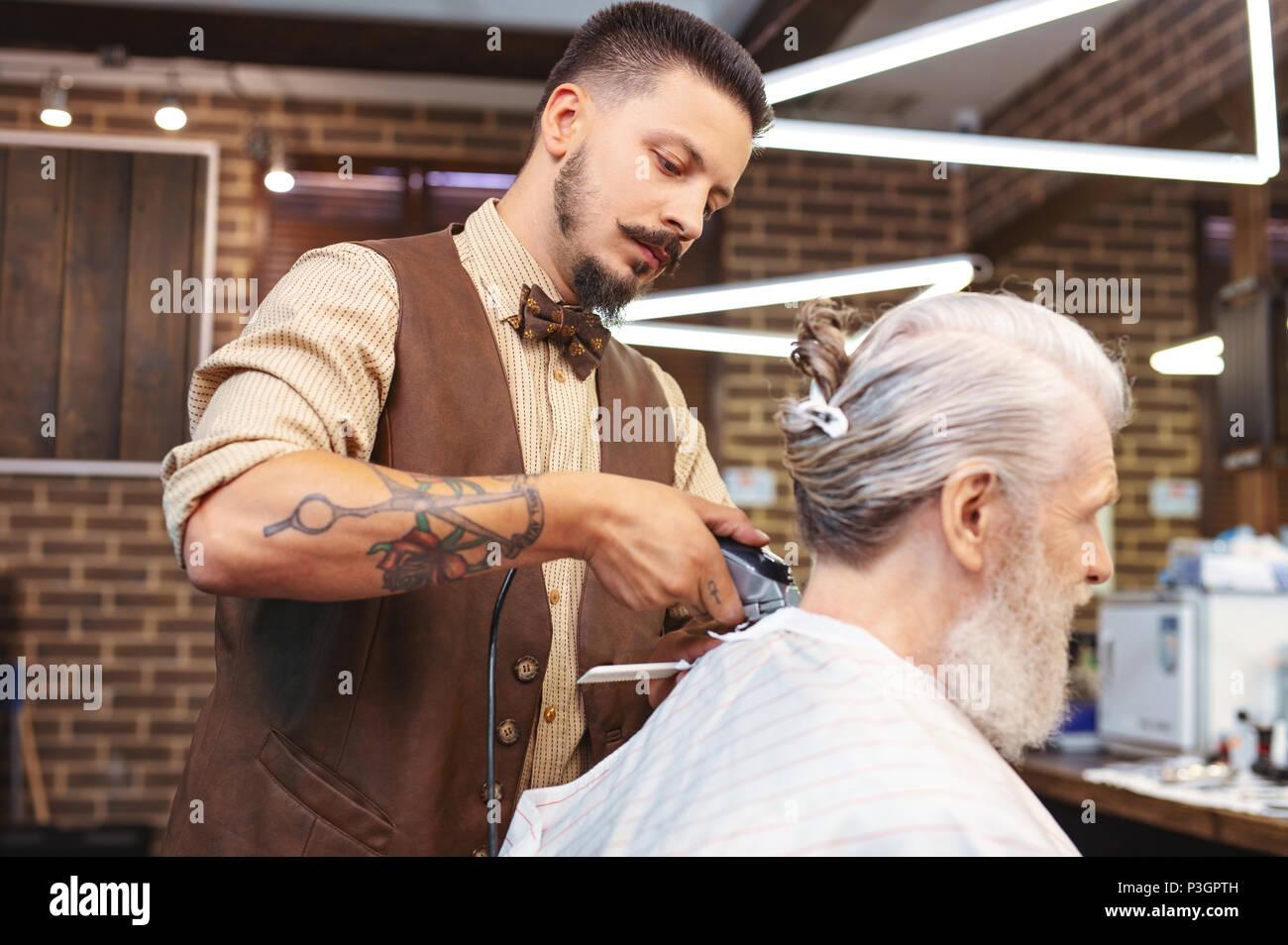 Konzentriert brunette männlichen Arbeiten im barbershop Stockbild