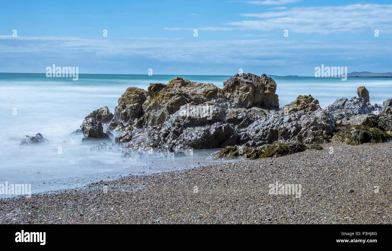Eine lange Aufnahme des Meeres waschen in um Felsen von Porth Nobla, Rhosneigr auf der Isle of Anglesey. Stockfoto