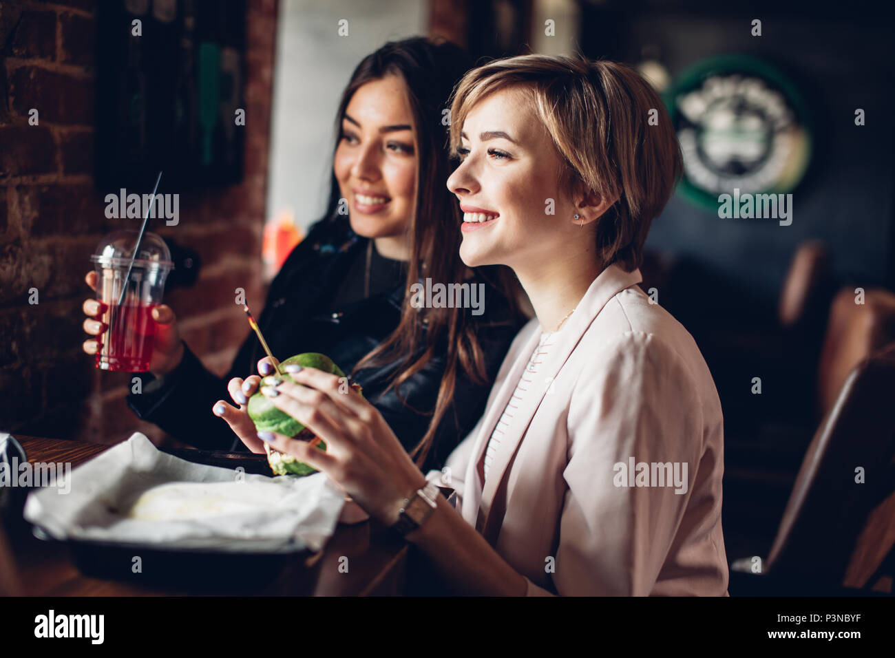 Zwei Freundinnen mit Abendmahl mit grünen Sandwich Burger Bar. Stockbild