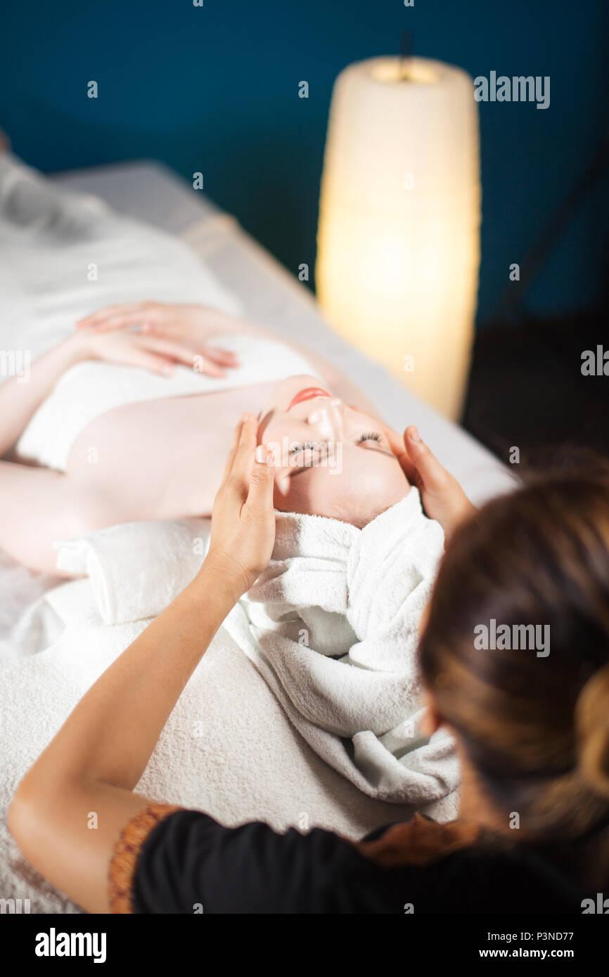 Gesunde Freizeit. Zufriedene Frau mit Gesicht Massage im Spa. Stockbild