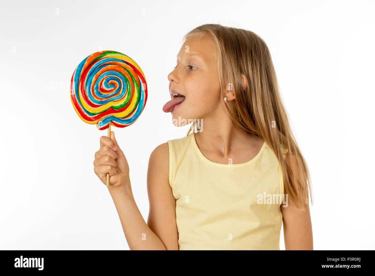 Nettes glückliches Kind mit Süßigkeiten Lutscher, glückliches Mädchen mit grossen Zucker Lutscher, Kid essen Süßigkeiten. Überrascht Kind mit Süßigkeiten. auf weißem Hintergrund, Stockfoto