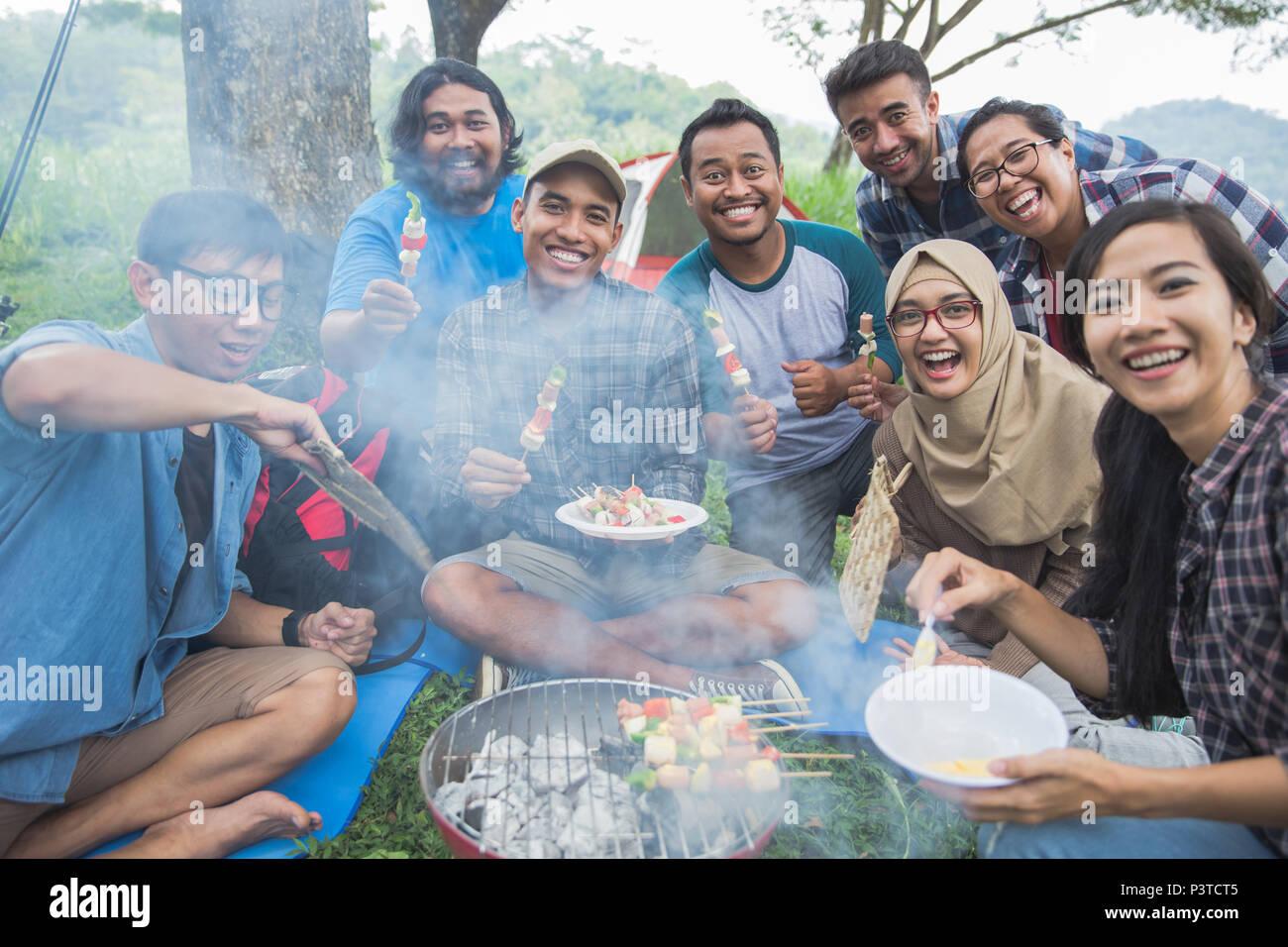 Barbecue im Wald beim zusammen Camping Stockbild