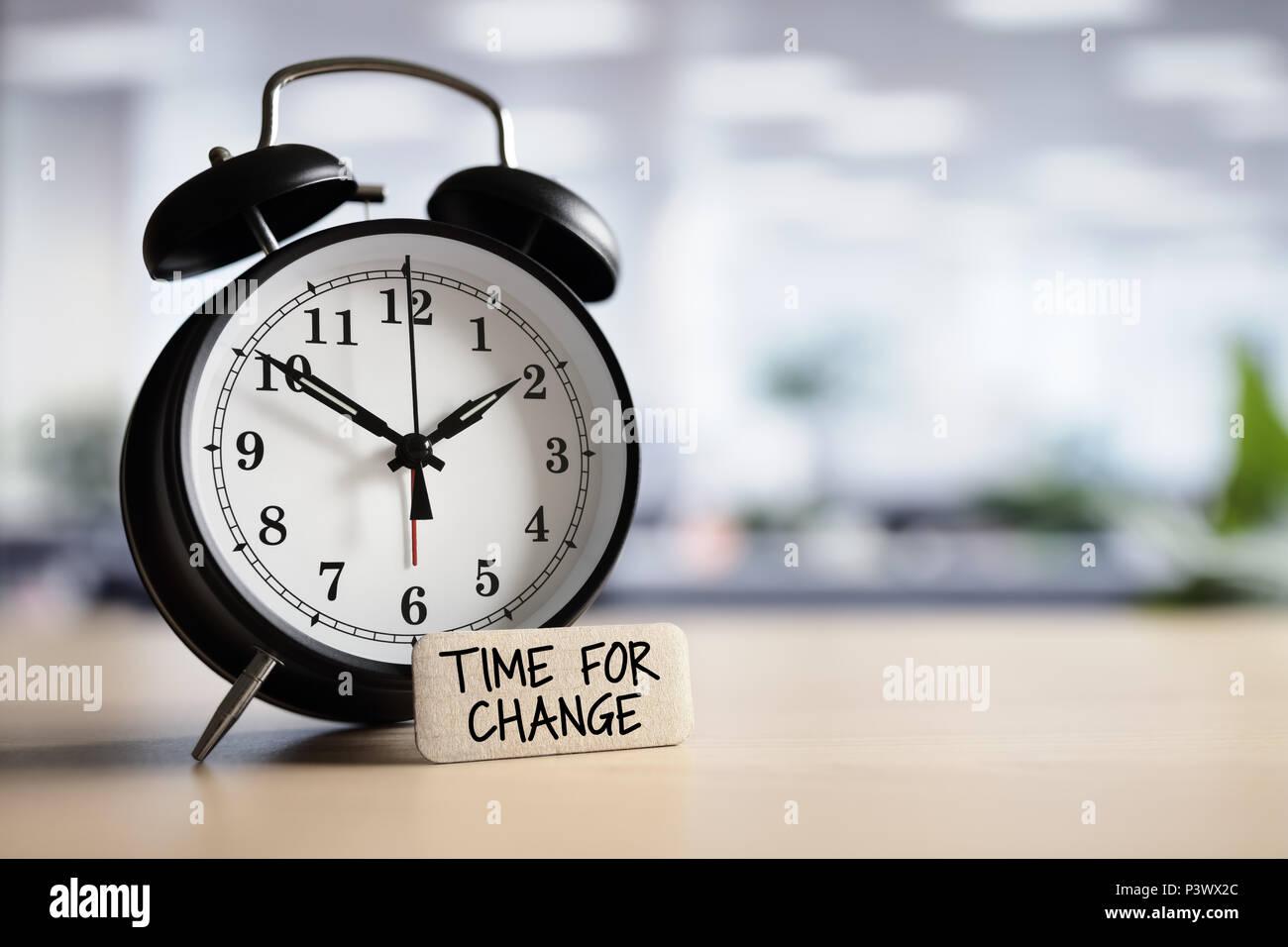 Zeit für Veränderungen oder action concept Nachricht mit Wecker auf dem Schreibtisch im Büro Stockbild