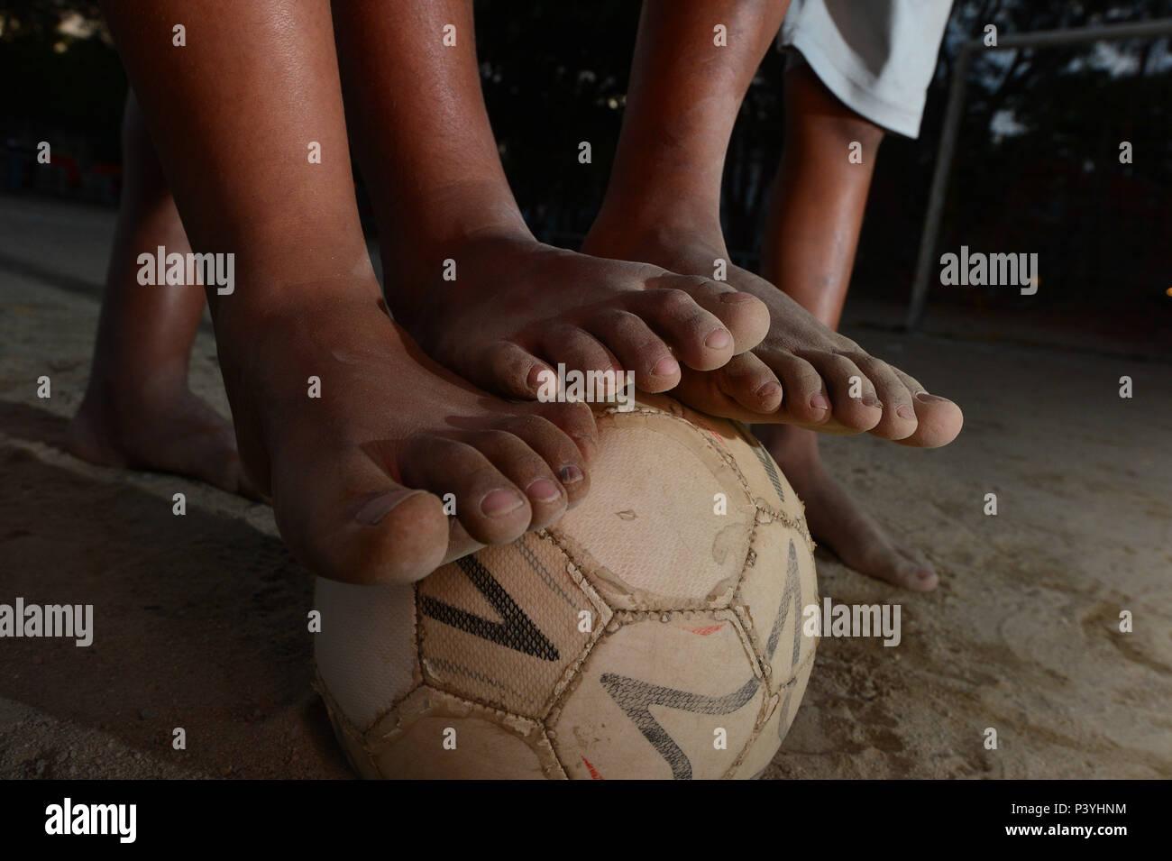 Da comunidade carente Crianças de Rio das Pedras na Zona oeste do Rio, com os pés sujos de Terra batida sobre uma Bola de Futebol. Stockfoto