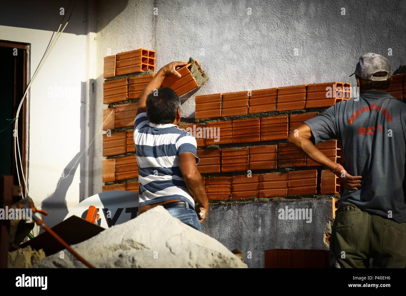 Pedreiros em construção de tijolos levantando Parede. Stockfoto