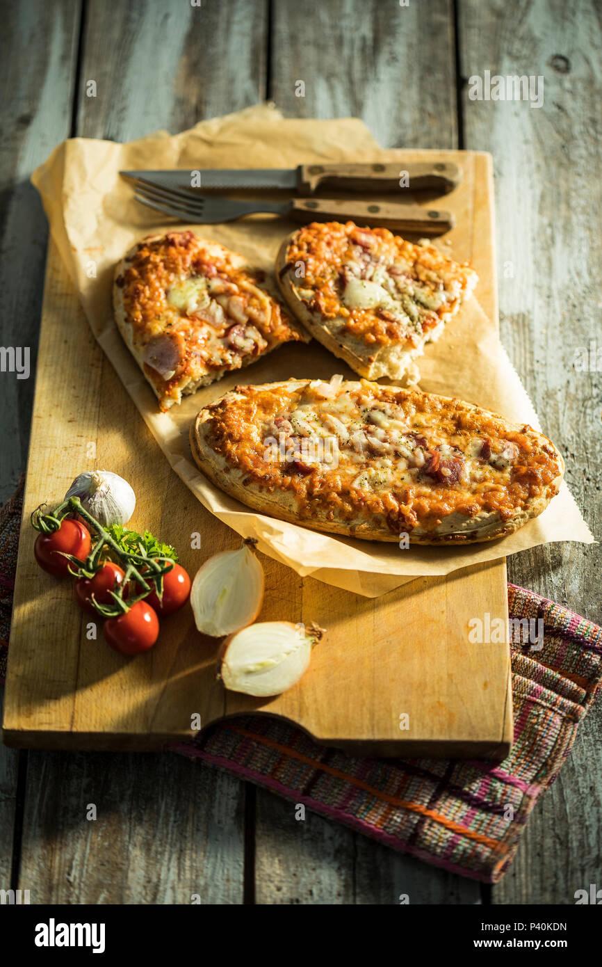 Rustikales Pizzabrot mit Salami, Käse, Zwiebeln und Tomaten/Paradeiser Stockbild