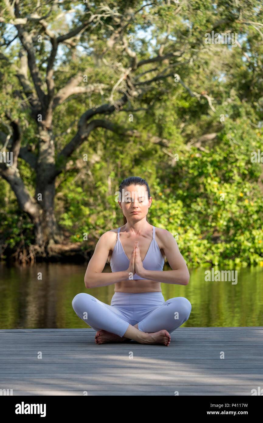 Frau sitzt an Deck durch Wasser Meditation und Yoga Stockbild