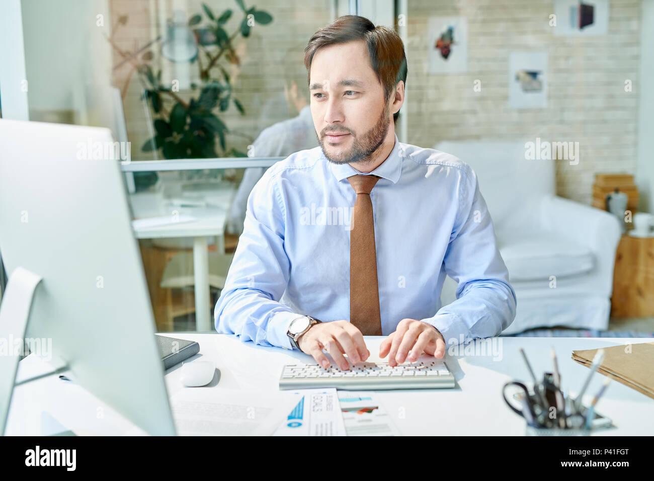 Elegante Geschäftsmanns, der auf dem Computer Stockbild