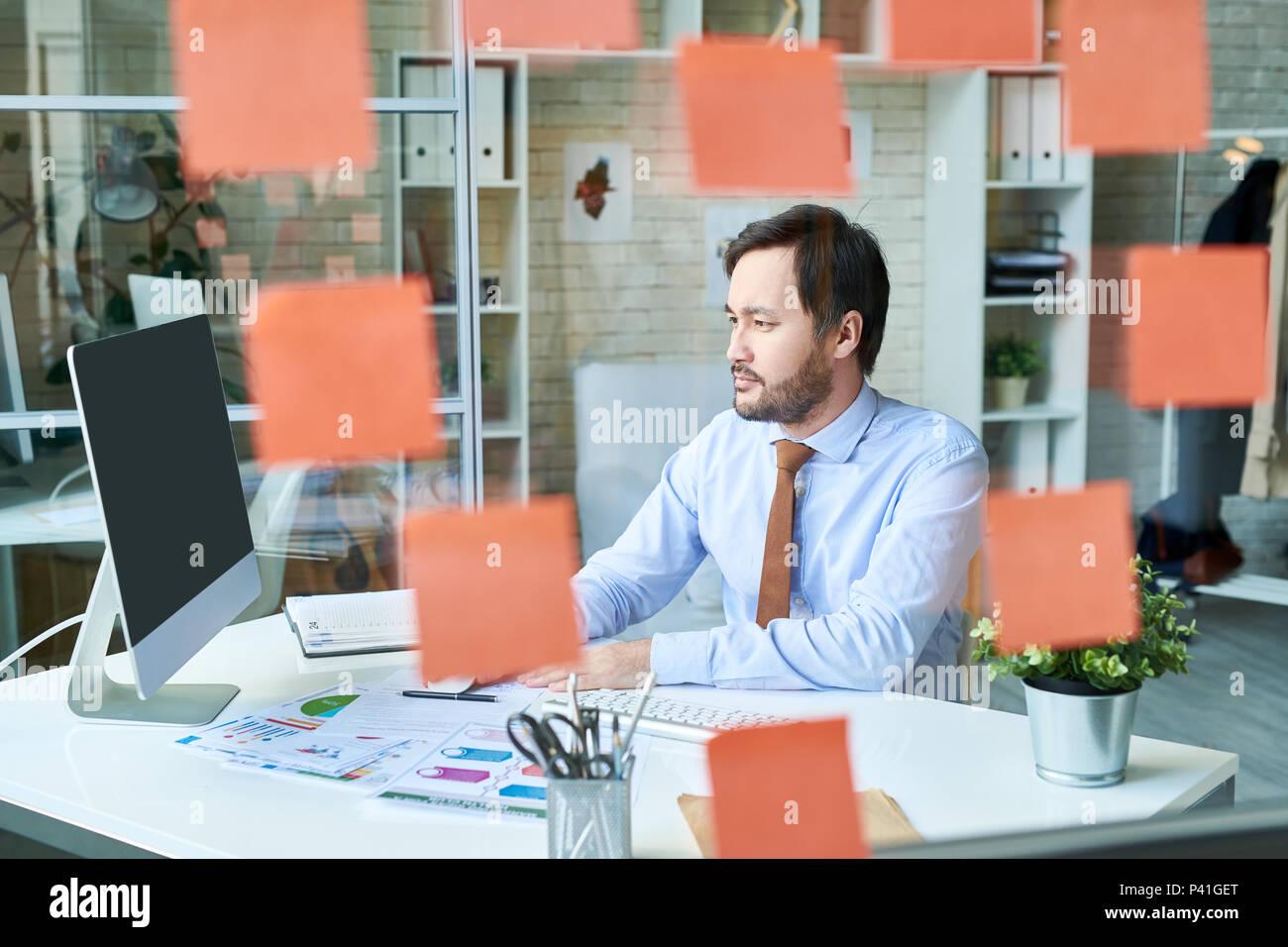 Mann im Büro hinter Glas arbeiten Stockbild