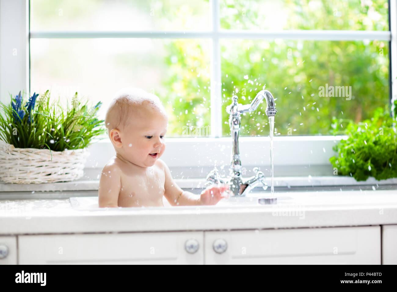Baby, Bad in der Küche. Kinder spielen mit Schaum und ...