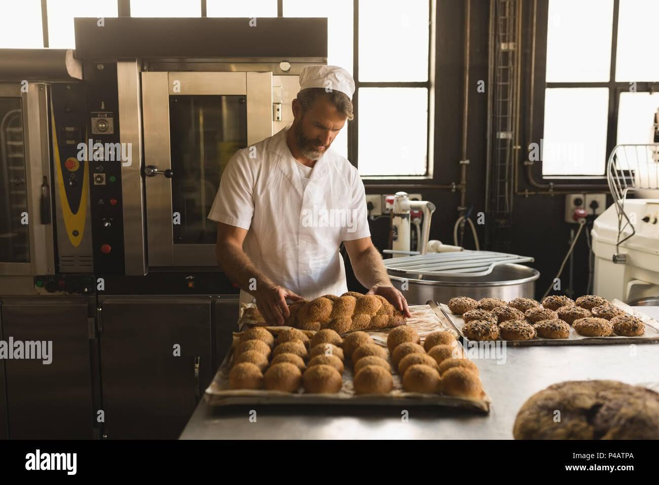 Männliche baker arrangieren gebackene süße Nahrungsmittel Stockbild