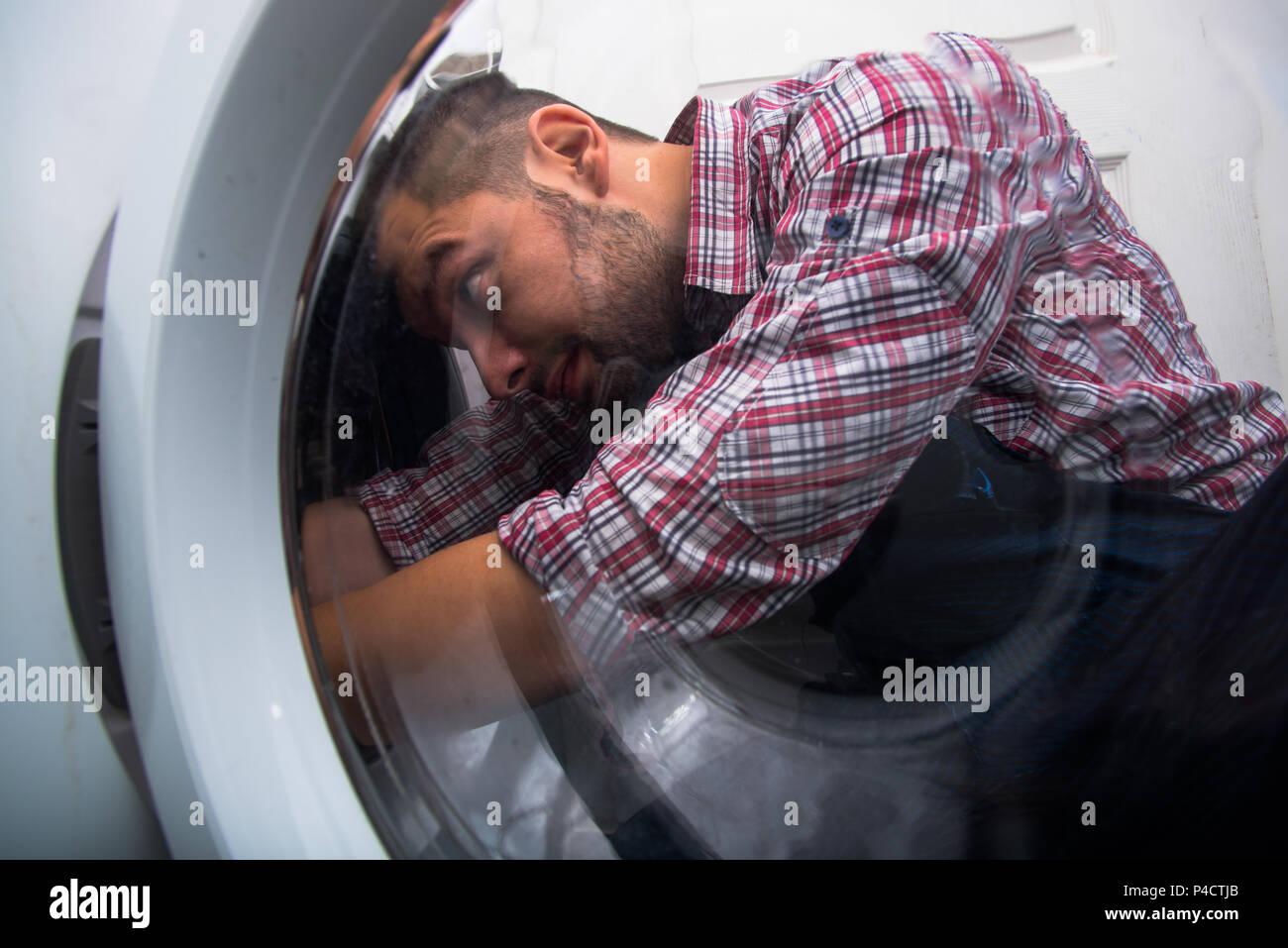 Reparatur der Mensch zur Festsetzung der Waschmaschine im Badezimmer Stockbild
