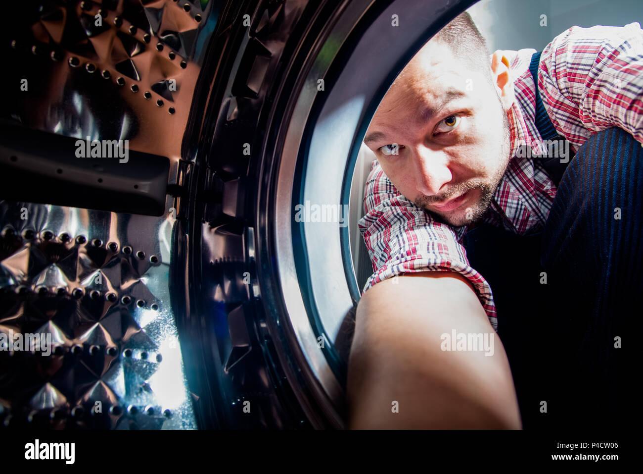 Reparatur der Mensch zur Festsetzung der Waschmaschine im Badezimmer, Blick von der Innenseite der Maschine Stockbild