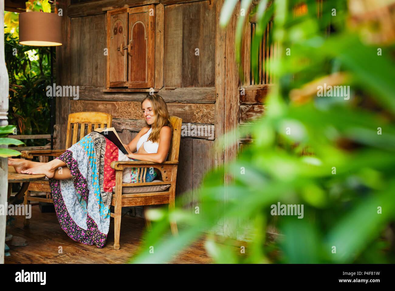 Attraktives Mädchen sitzen auf der Veranda des Bungalows mit tropischem Gartenblick, Romanze in Papier Buch lesen. Junge Frau, die sich in Luxus Villa Stockbild
