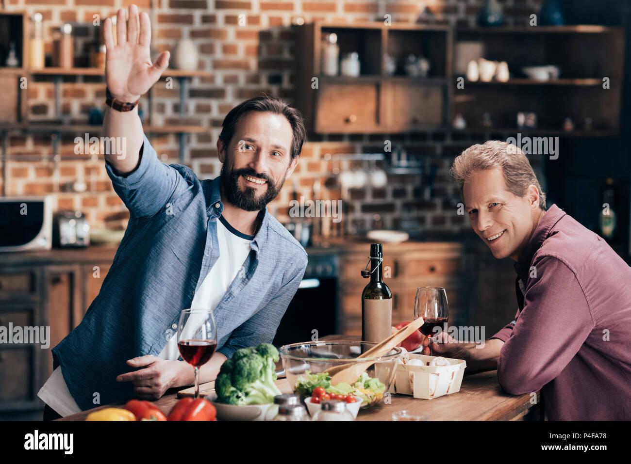 Freundliche Männer mittleren Alters, Wein trinken und winkende Hand, während das gemeinsame Kochen in der Küche Stockbild