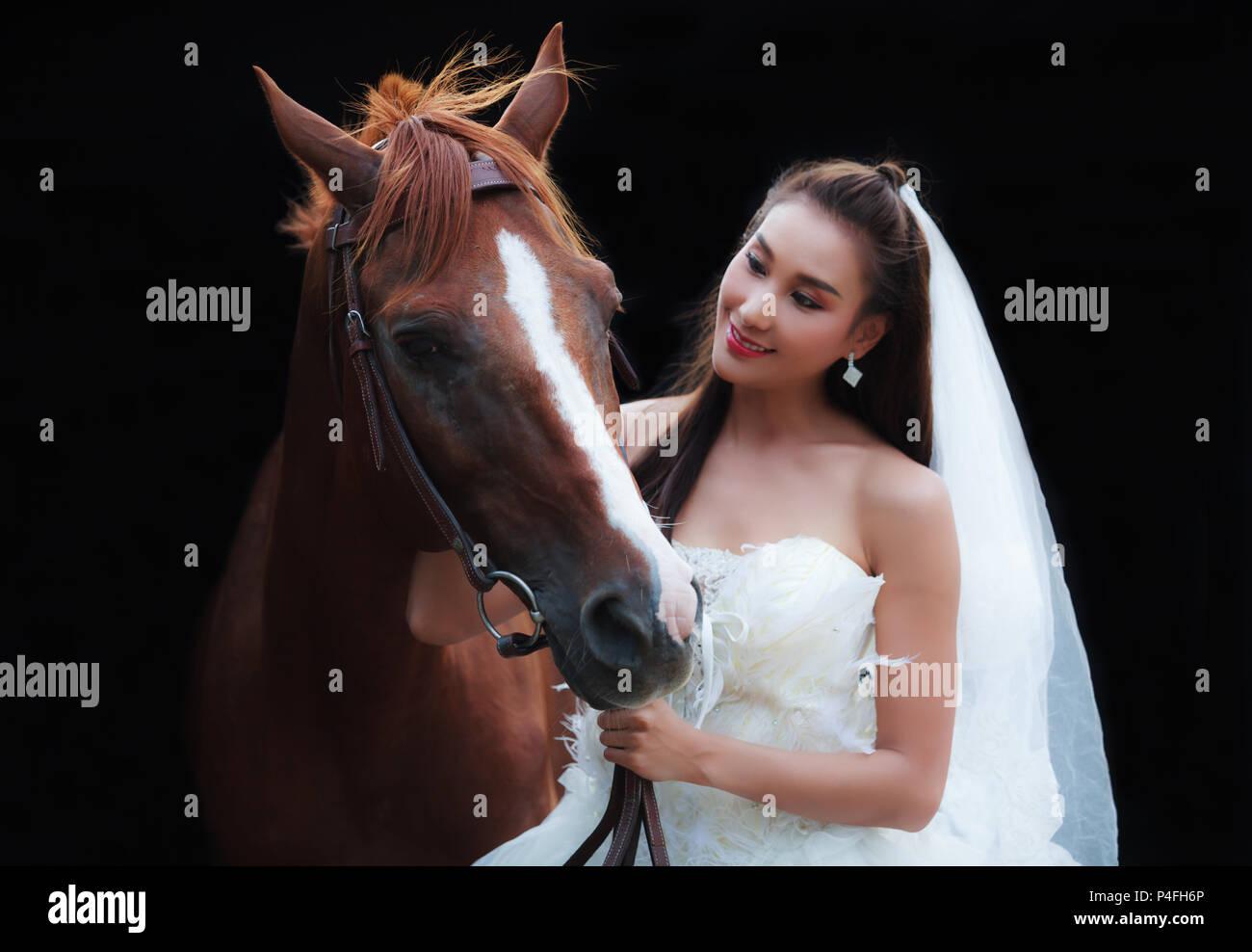 Junge schöne Schönheit Braut fashion White Wedding Kostüm stehen mit den stattlichen Pferd auf schwarzem Hintergrund Stockfoto