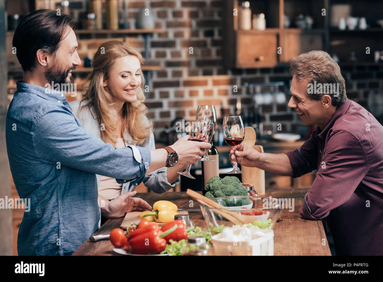 Lächelnd kaukasischen Freunde trinken Wein beim Kochen Abendessen Stockbild
