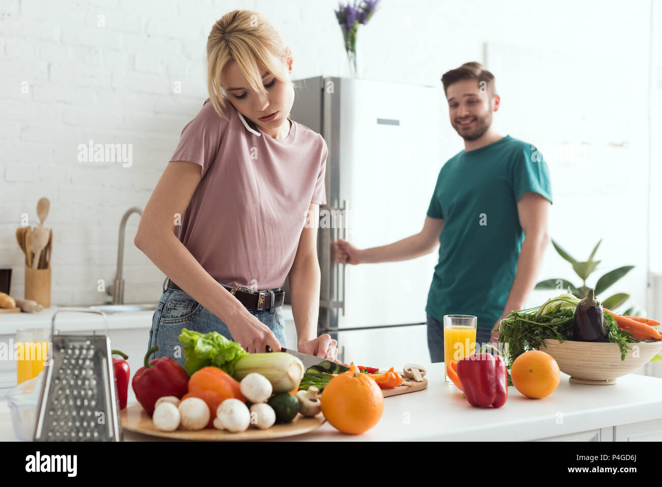 Vegan Freundin sprechen von Smartphone beim Kochen Salat an Küche Stockbild