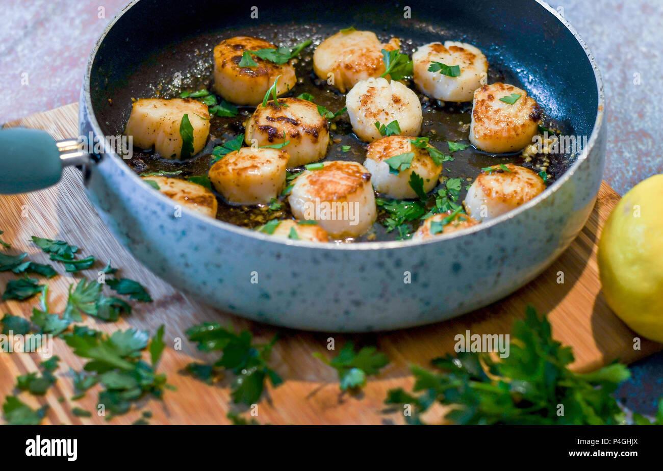 Sengende Jakobsmuscheln in einer Pfanne; Hausgemachte Gourmetgerichte Stockbild