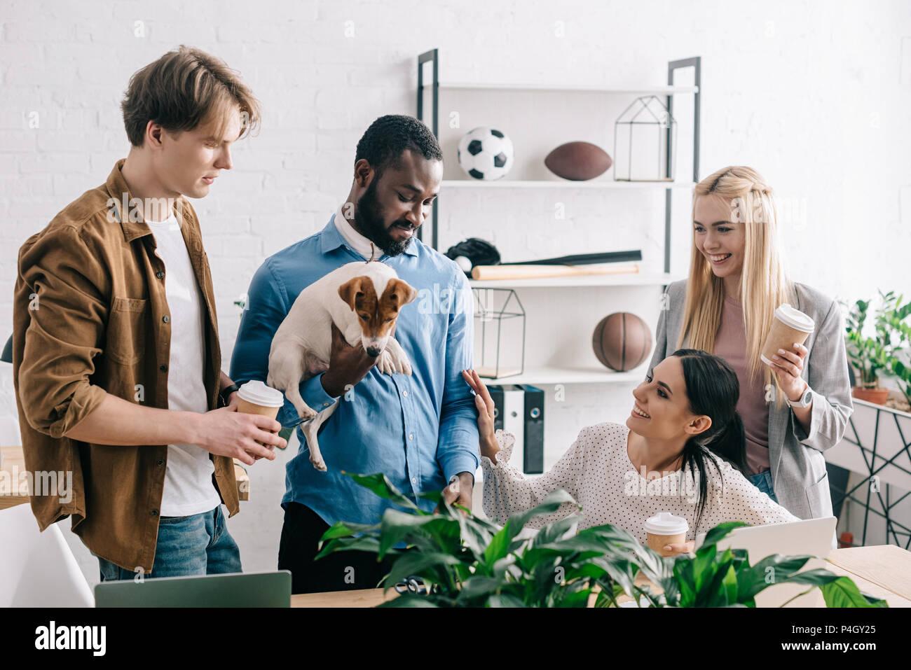 Afrikanische amerikanische Geschäftsmann holding Jack Russell Terrier und lächelnd Kollegen in der Nähe von ständigen Stockbild