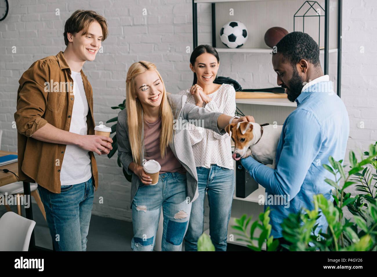 Afrikanische amerikanische Geschäftsmann holding Hund von lächelnden und Kollegen mit Kaffee Tassen umgeben Stockbild