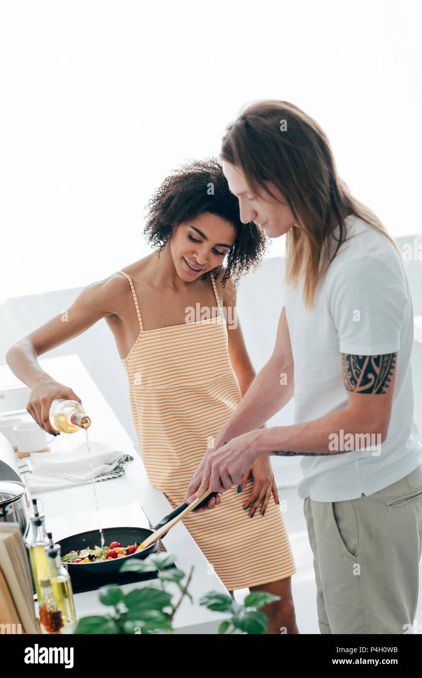 Afrikanische amerikanische junge Frau gießen Wein auf Pfanne während Freund Kochen in der Küche Stockbild