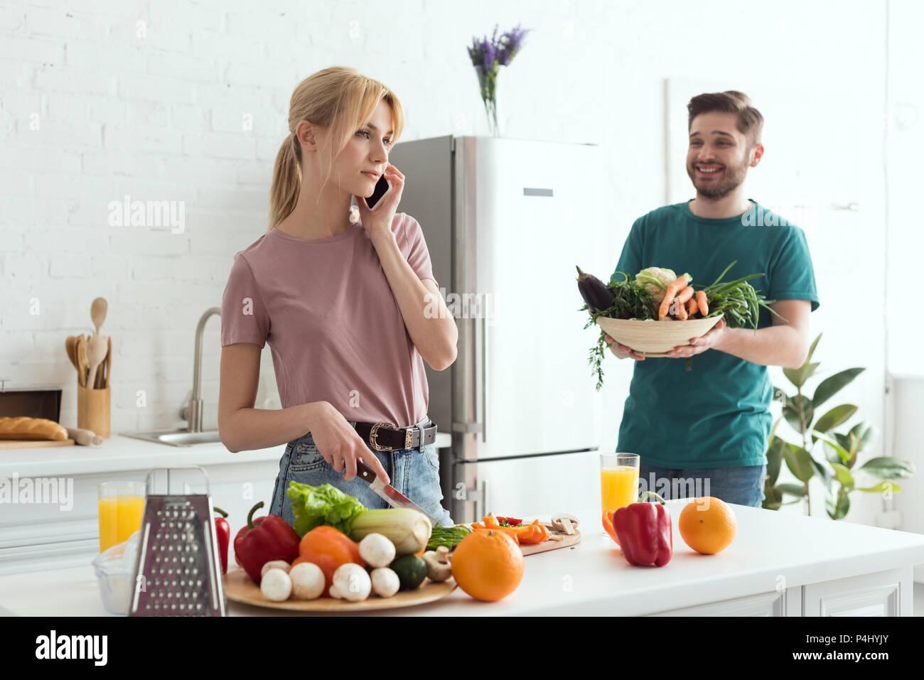Vegan Freundin sprechen von Smartphone beim Kochen in der Küche Stockbild