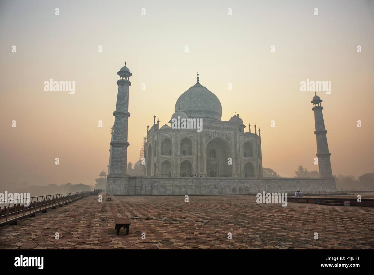 Agra, Indien. Weißer Marmor Taj Mahal Komplex mit Minaretten und Wänden durch den Dunst und Smog von Agra Fort Festung UNESCO Weltkulturerbe Stockbild