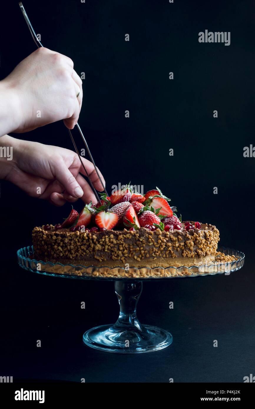 Eine Schokolade Kuchen gekrönt mit Erdbeeren, Granatapfel Samen und Nüsse Stockbild