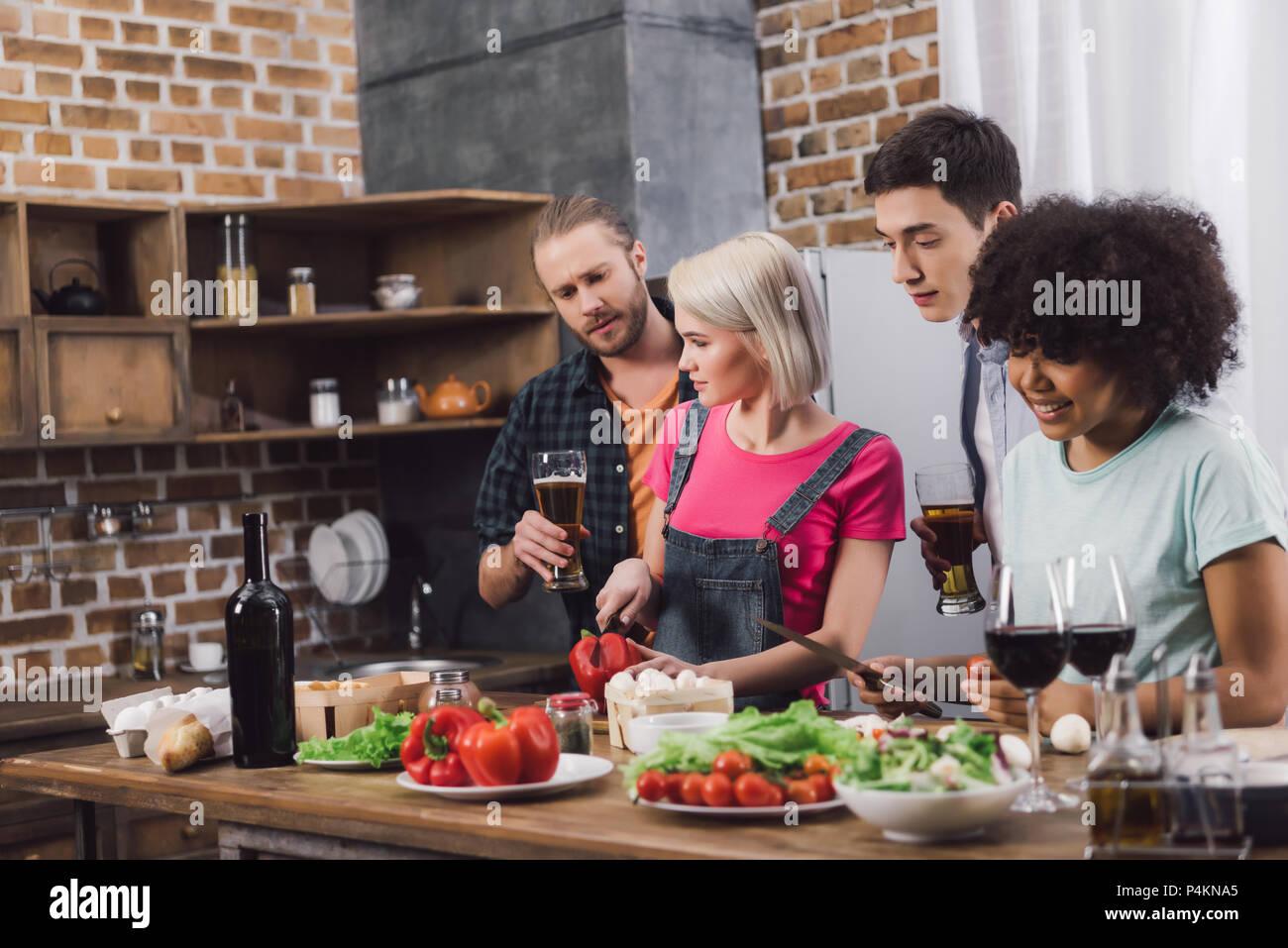 Männer mit Bier, wie multiethnischen Mädchen kochen Stockbild