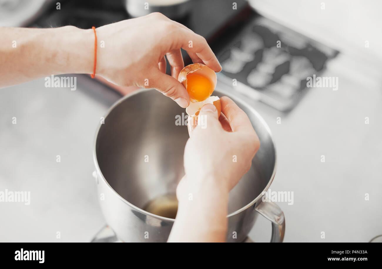 Cook gießt yalk des Eies in Metallplatte Stockbild