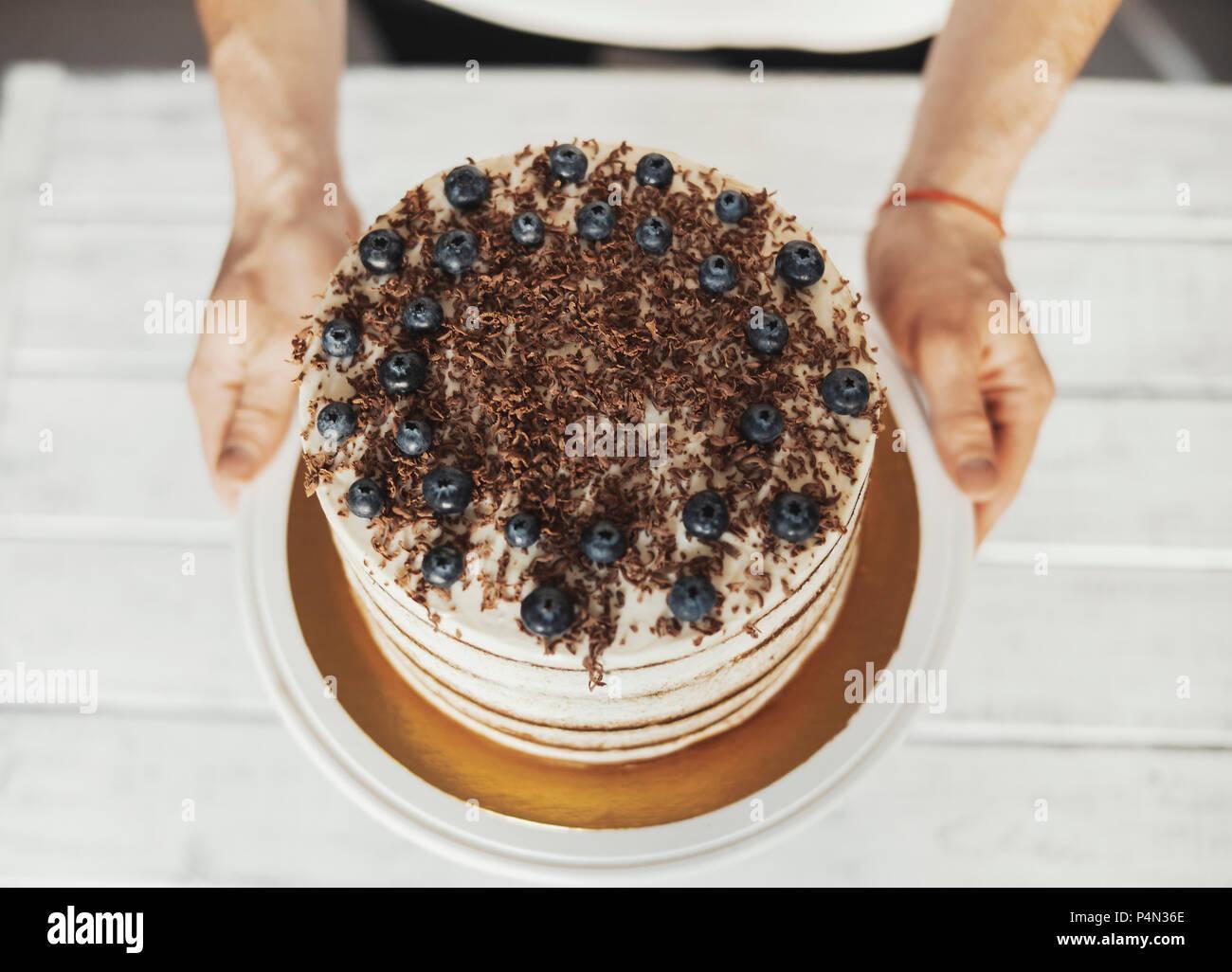 Jungen attraktiven Mann dekorieren Kuchen mit Schokolade und Beeren Stockbild