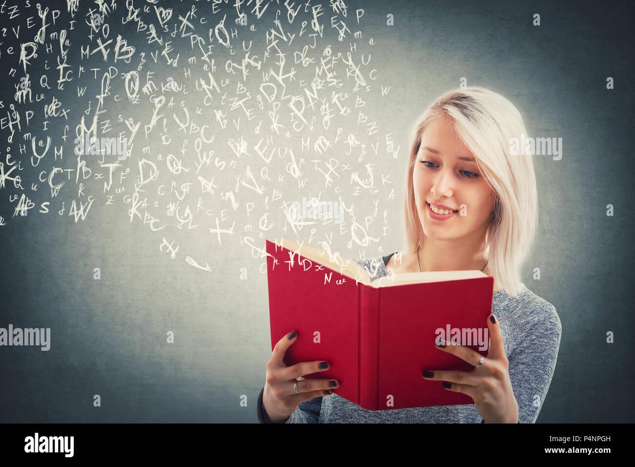 Schöne blonde Mädchen lesen und fliegende Buchstaben des Alphabets Flucht aus dem Roten Buch. Die Magie der Vorlesung. Junge Lehrer studieren, Bildungs- und Stockbild