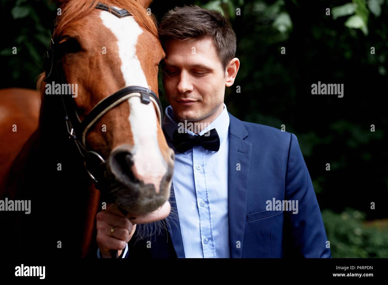 Hochzeit romantischen Spaziergang von Braut und Bräutigam. Braunes Pferd. Portrait von Bräutigam Stockbild