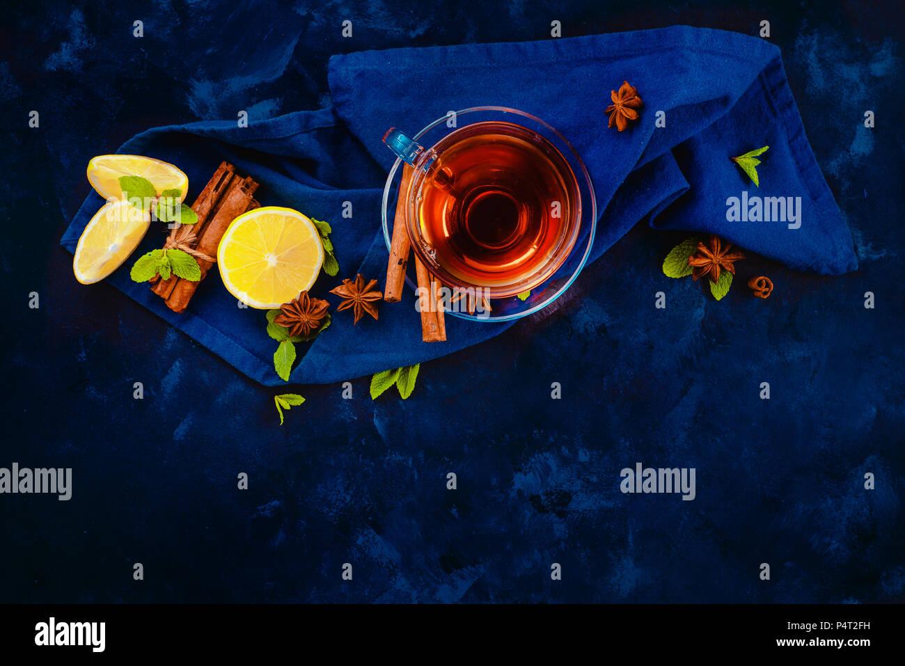 Heißes Getränk Header mit Glas Teetasse, , Serviette, Zitronenscheiben, Zimt, Anis Sterne und Minze auf einem dunklen Hintergrund. Dunkle essen Fotografie flach Stockbild
