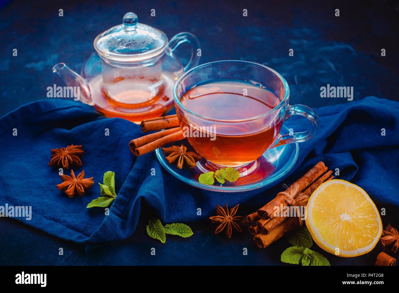 Schwarzer Tee Glas Teetasse, , Serviette, Zitronenscheiben, Zimt, Anis Sterne und Minze auf einem dunklen Hintergrund. Dunkle essen Fotografie Header mit kopieren Stockbild