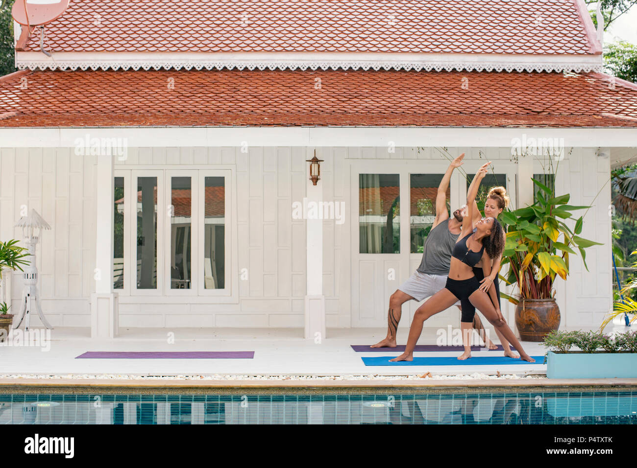 Yogalehrer lehre Frau richtige yoga Pose auf der Terrasse Stockbild