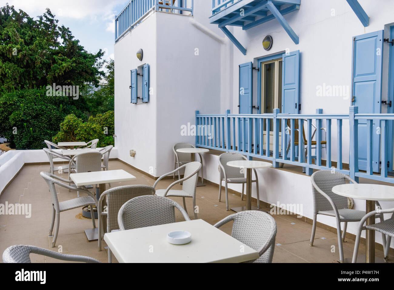 Mykonos, Griechenland traditionelle Apartment Haus externe Ansicht. Hotel Atrium mit weißen Wänden und blauen Balkon mit Stühlen und Tischen. Stockbild