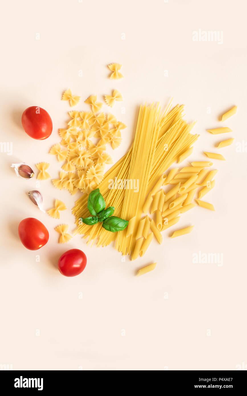Verschiedene roh Rohe Nudeln mit Basilikum, Tomaten und Knoblauch auf Rosa pastell Hintergrund. Italienische Pasta: Penne, Farfalle, Spaghetti. Stockbild