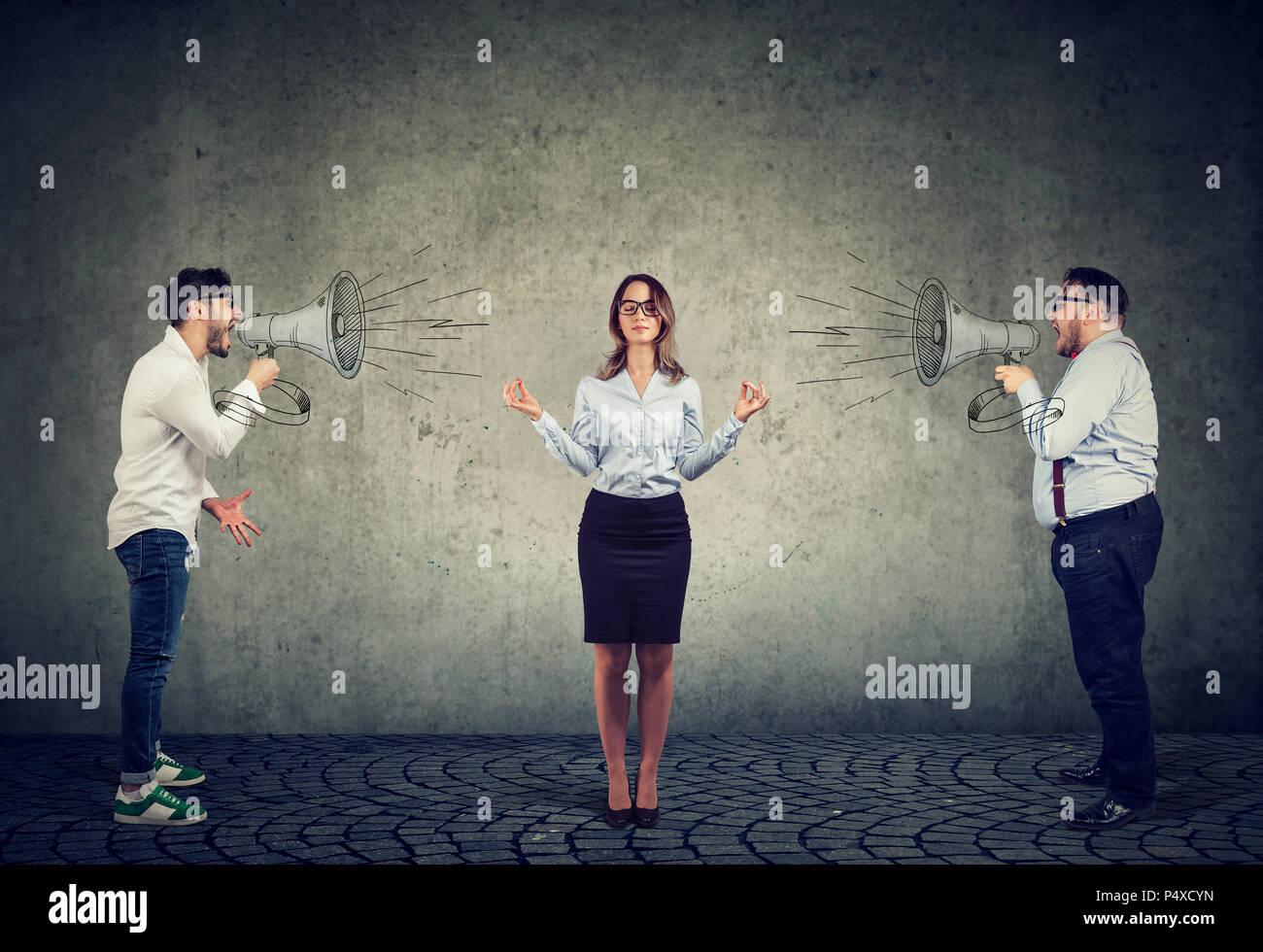 Meditieren junge geschäftsfrau zahlen keine Aufmerksamkeit auf zwei böse Männer an ihr Megaphon schreien Stockbild