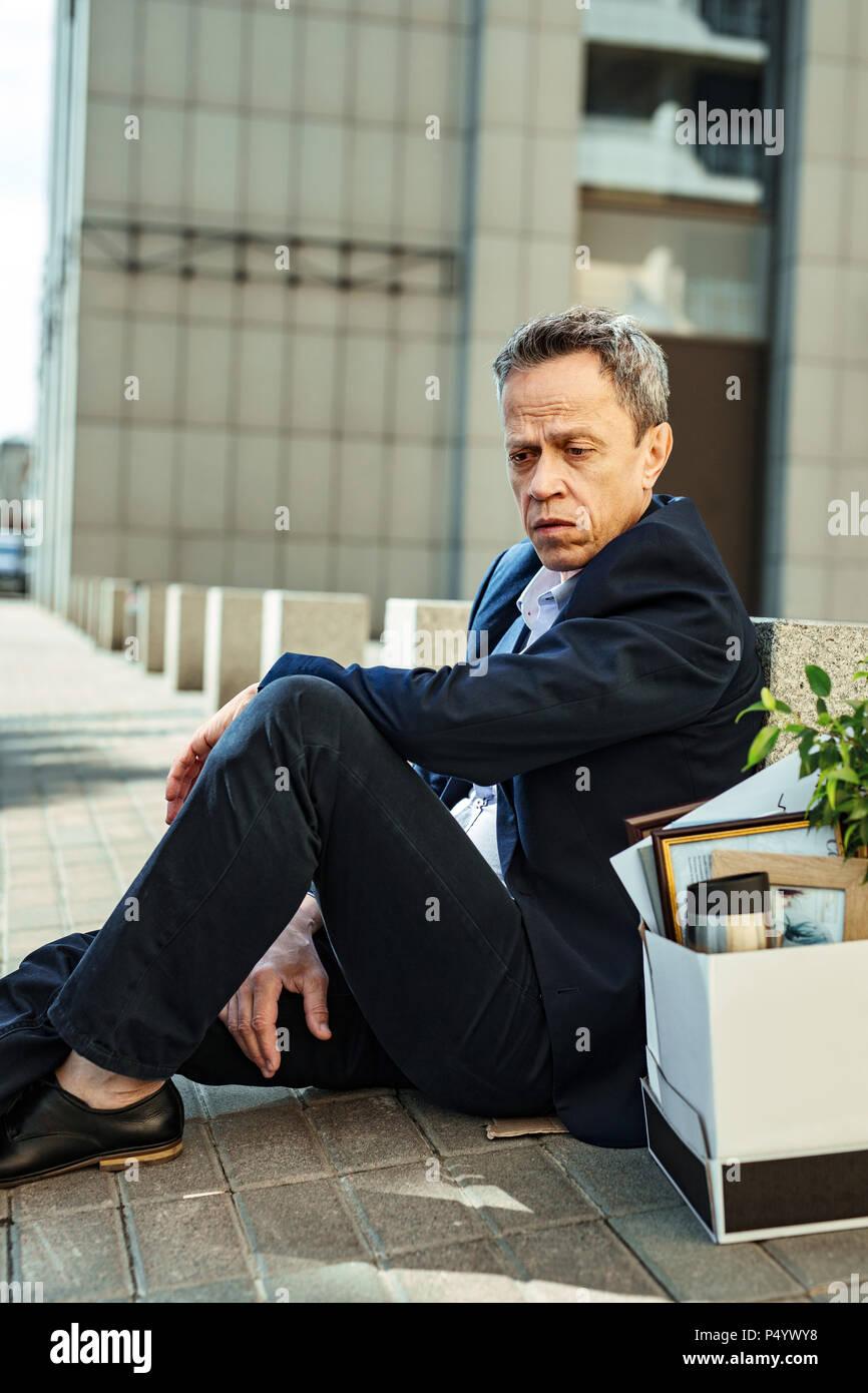 Ältere Mann in schwarzen Jeans verloren Gefühl nach abgefeuert werden Stockbild