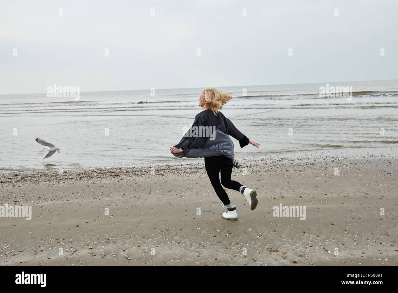 Niederlande, glücklich, blonde junge Frau, die auf den Strand Stockbild