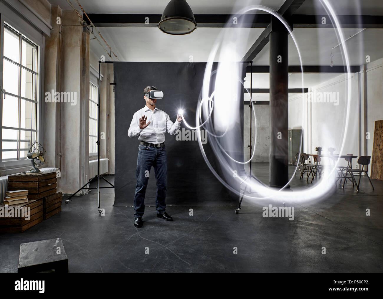 Reifer Mann mit VR-Brille Licht Malerei vor schwarzem Hintergrund auf dem Dachboden Stockbild