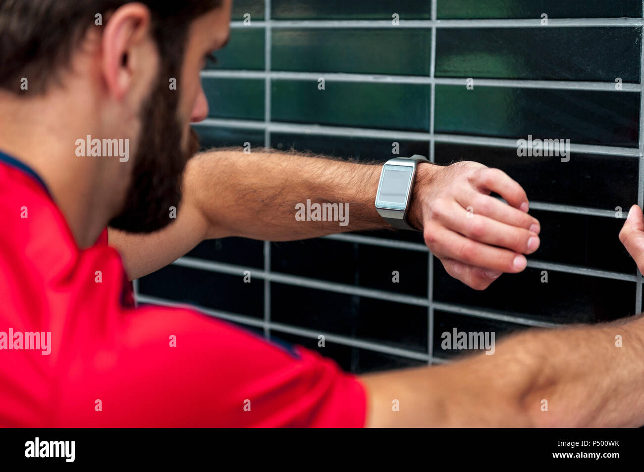 Mensch, der hatte eine Pause von der laufenden Kontrolle der Zeit auf einem smartwatch Stockbild