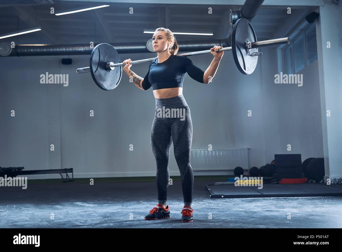 Frau üben Langhantel squat im Fitnessstudio Stockbild