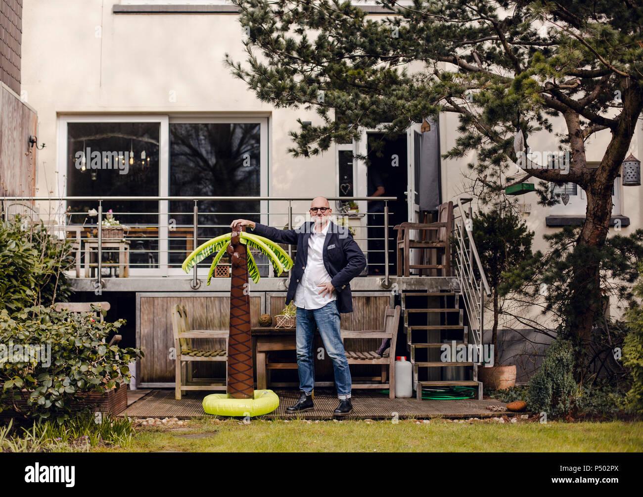Senior Geschäftsmann Steht In Seinem Garten Mit Einem Gummi Palm