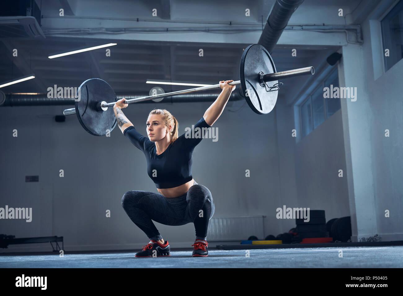 Frau tun Overhead hocke Übung im Fitnessstudio Stockbild