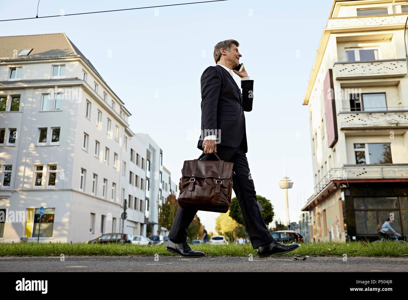 Reifen Geschäftsmann wandern und Sie ihr Smartphone in der Stadt Stockbild